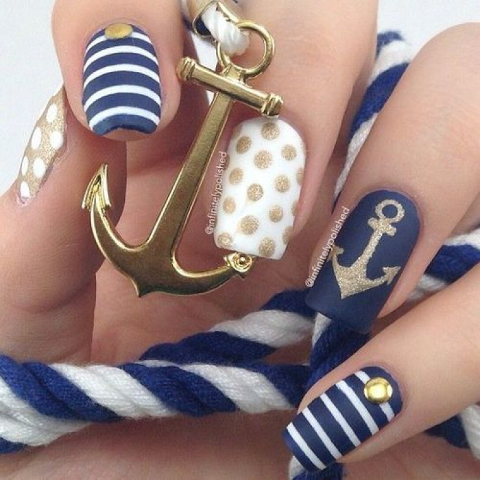 Navy nail art with anchor, stripes and polka dots in blue theme